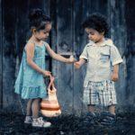 Girl giving boy a dandelion clock
