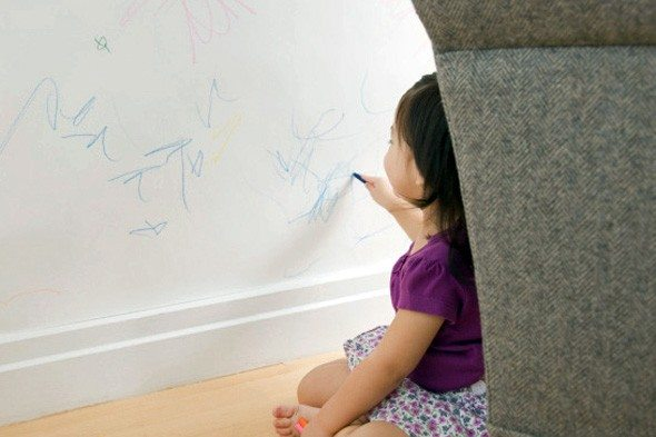 A little girl drawing on a wall with a crayon