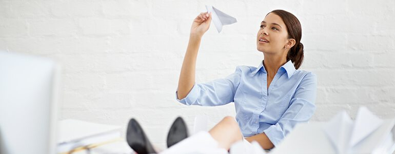 Woman making and throwing paper aeroplanes