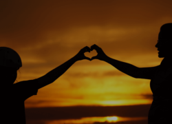 People holding hands in front of a sunset