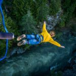 A person bungee jumping into a river